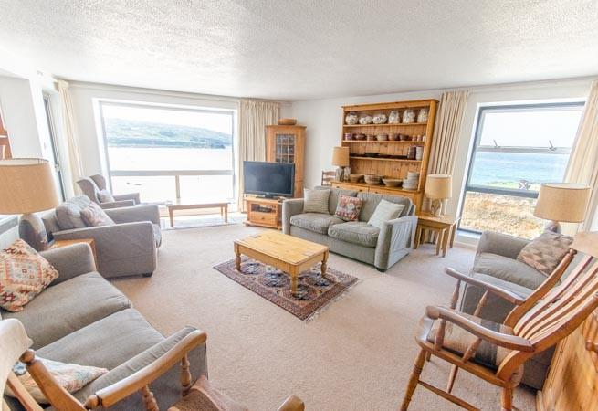 Bright dual aspect sitting room with uninterrupted views over Portmeor.