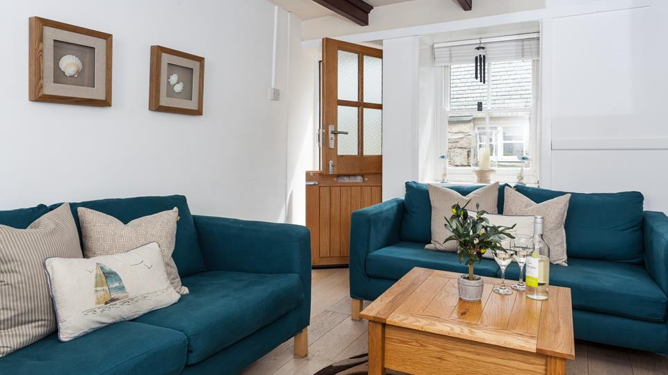the living space has two textile sofas with a solid natural wood coffee table and natural oak flooring.