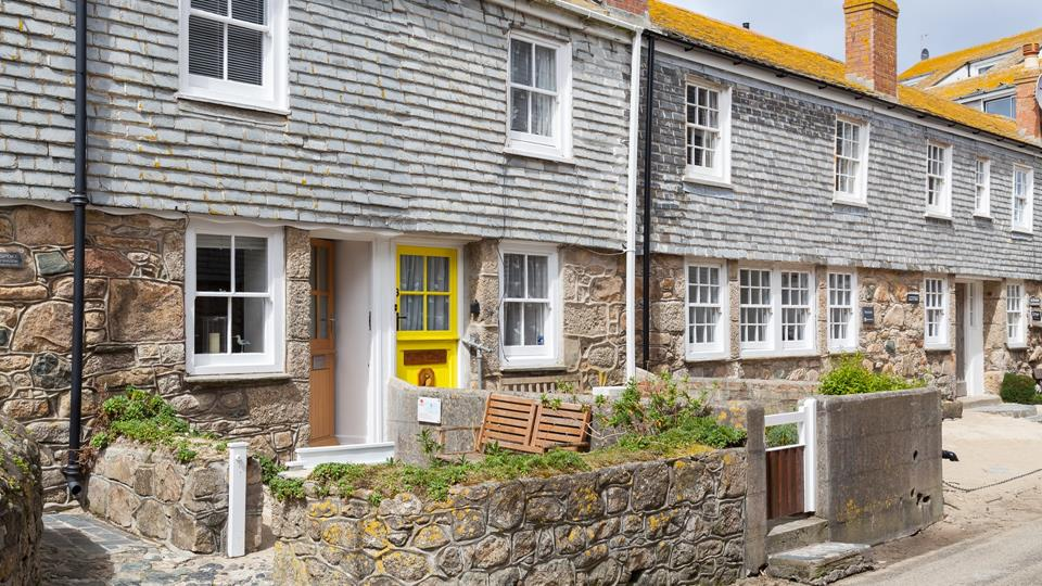 The cottage is a pretty terraced cottage with slate-hung cladding, traditional oak stable door with granite stone facing.