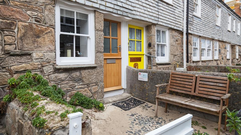 Polly's Cottage has a pretty cobbled front courtyard with a teak wood bench seat and a small painted wood front gate.