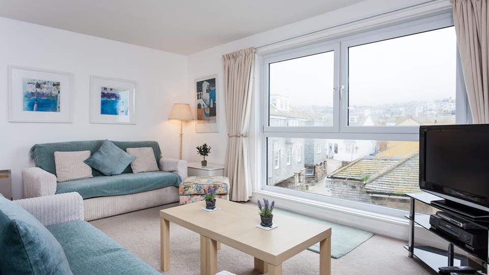 The living space has two textile sofas and a natural light wood coffee table, a large window overlooks the pretty town.