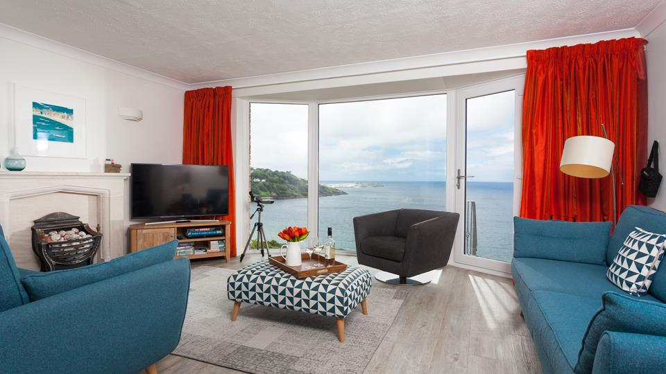 Floor to ceiling windows display stunning views of Carbis Bay and beyond, with a door leading to the private patio area.