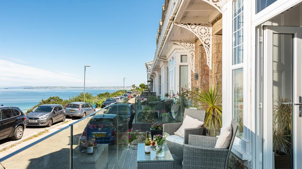 French doors lead out onto a small balcony area with views of Godrevy Lighthouse and St Ives Bay.