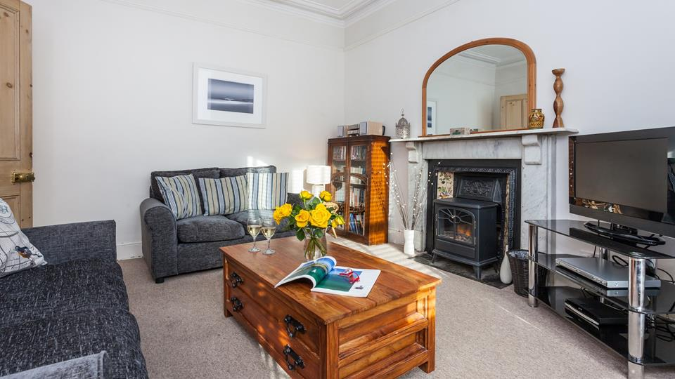 The sitting room area has two grey textile sofas, a solid natural wood coffee table chest and an electric stove effect fire.