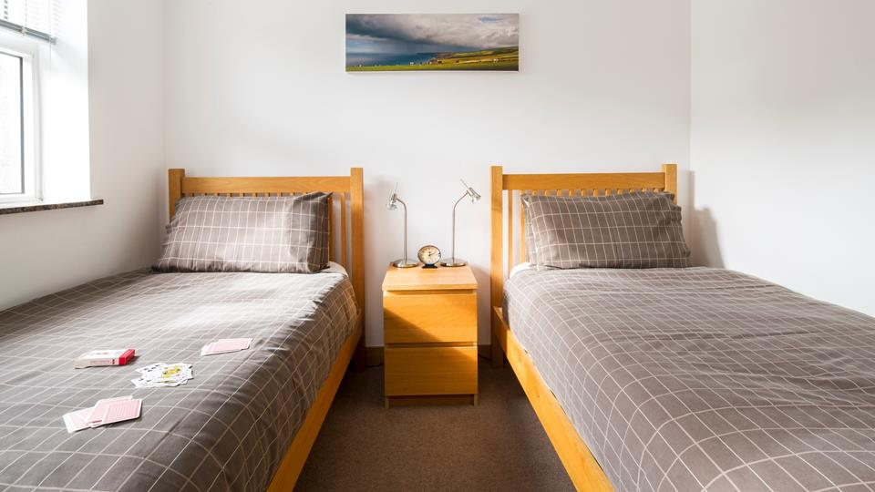 Bedroom two has wooden bedstead twin beds and the bedside chest has two contemporary style metal bedside lamps.