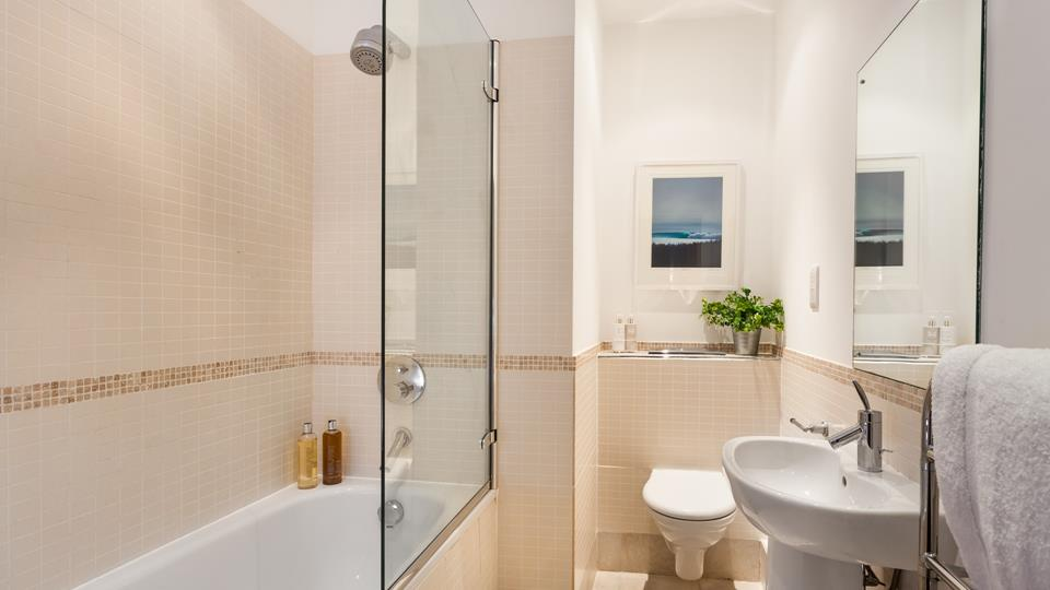 The bathroom has a well-sized bath with shower over and a large mirror over the basin.