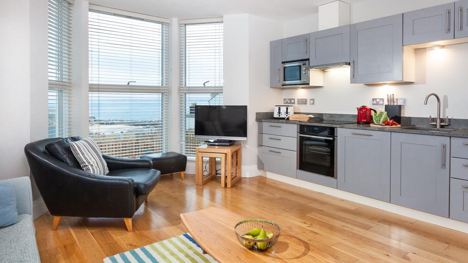 The living space is very modern, there is a black leather armchair with matching footstool next to the floor to ceiling bay window with views towards the Harbour.