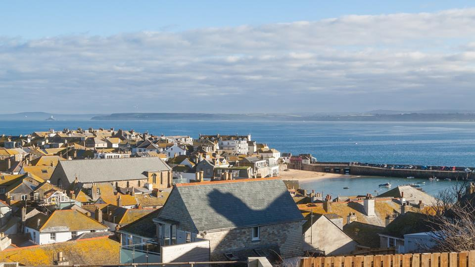 A picturesque view of the rooftop of St Ives leading down towards the Harbour with Godrevy Lighthouse in the distance.