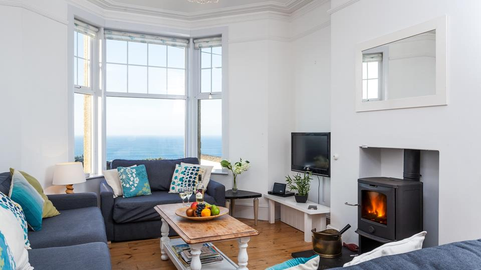 The sitting room has a stunning view over Porthmeor beach, three sofas and a wood burner to cosy up next to.