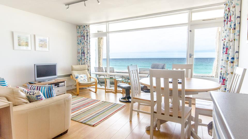 Open plan sitting/dining area with a door to the large balcony directly above Porthmeor beach.