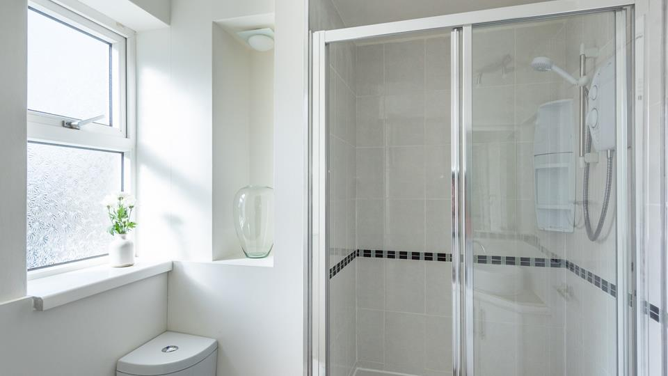 Large shower enclosure in the shower room with an electric shower and a handy corner shelf unit.