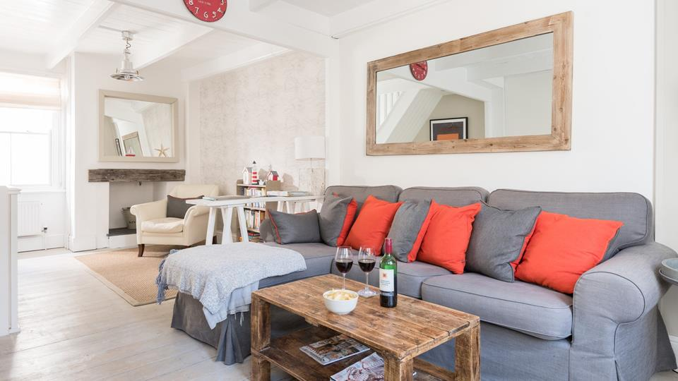 The living space has a grey textile corner sofa, reclaimed wood coffee table and statement mirror.