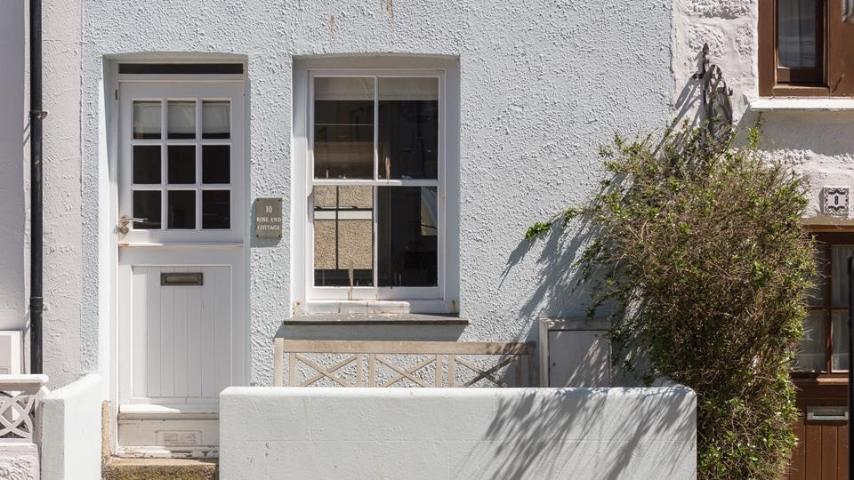 Rose End Cottage has a white painted stable door with a traditional sash-style window and pale blue whitewashed facade.