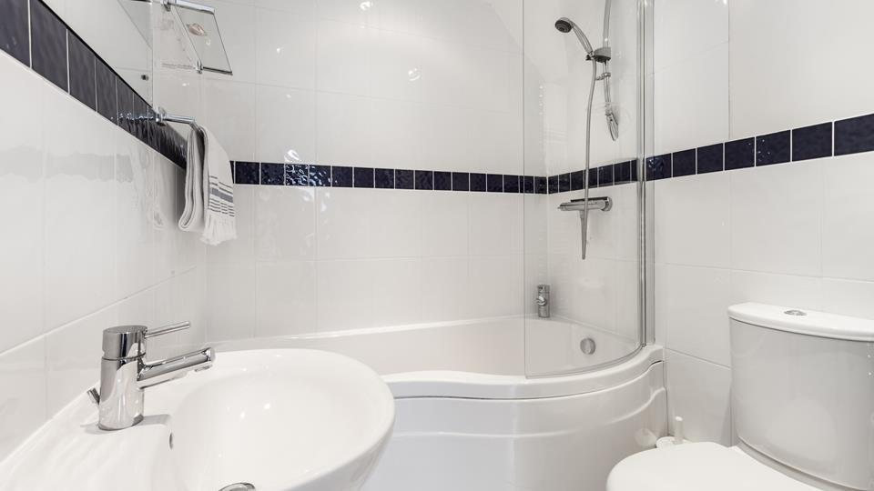 The bathroom benefits from both a bath and shower over, perfect for a bubbly soak after a day stomping the coastal paths.