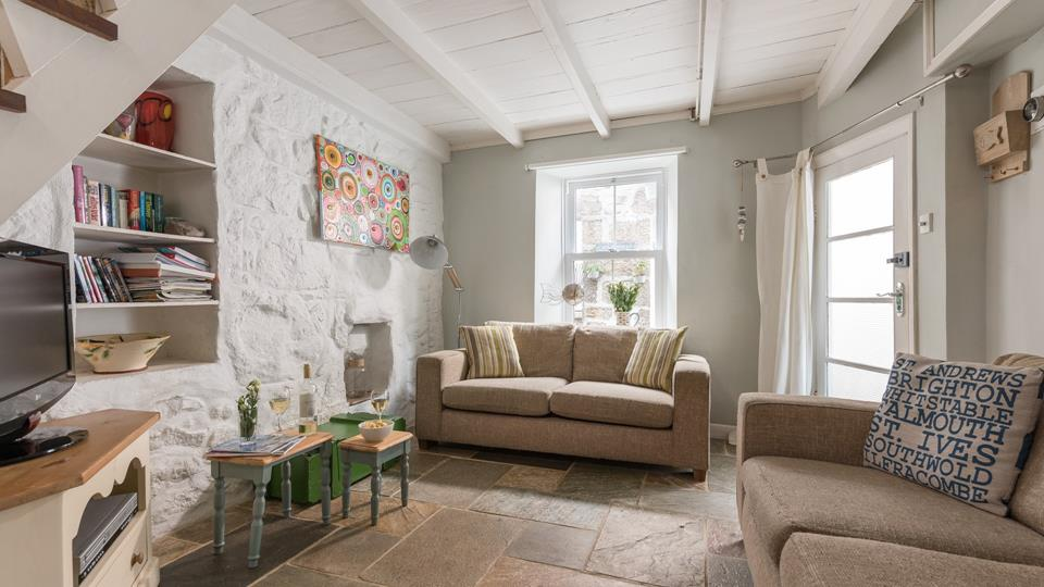 The living space has painted exposed beams and a traditional style sash window, the entrance door is glazed.