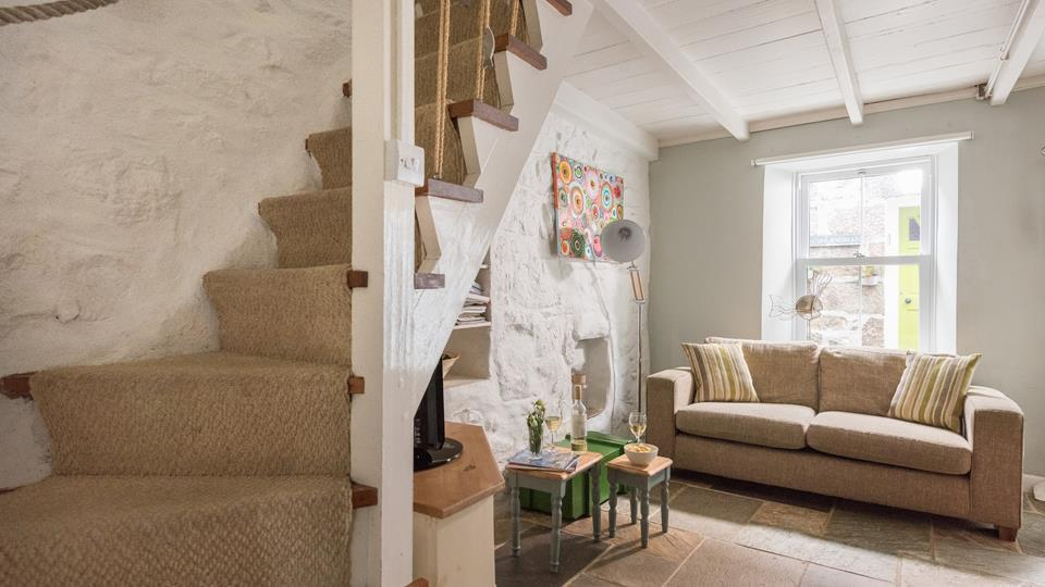 The living space has a quarry stone floor and a painted exposed stone-faced accent wall with open shelves and alcove.