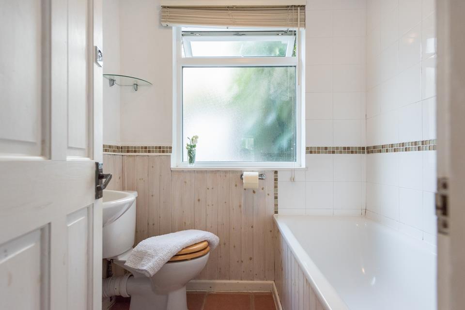 The ground floor bathroom has a bath with shower over.