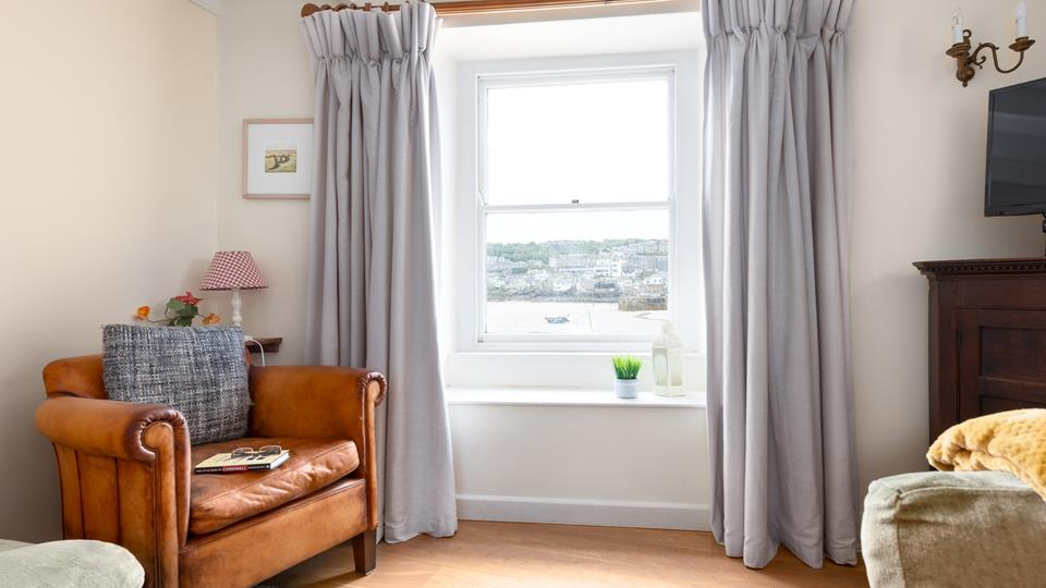 Opulent curtains frame the sash window overlooking St Ives Harbour and beach - a stunning view.
