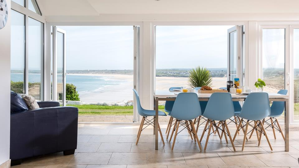 Double bi-folding doors open out from the living space with a panoramic sea view over Carbis Bay and far beyond along the coastline.