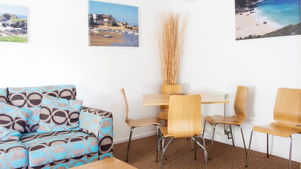 The living space has a retro style textile sofa and a metal and wood table and chairs.