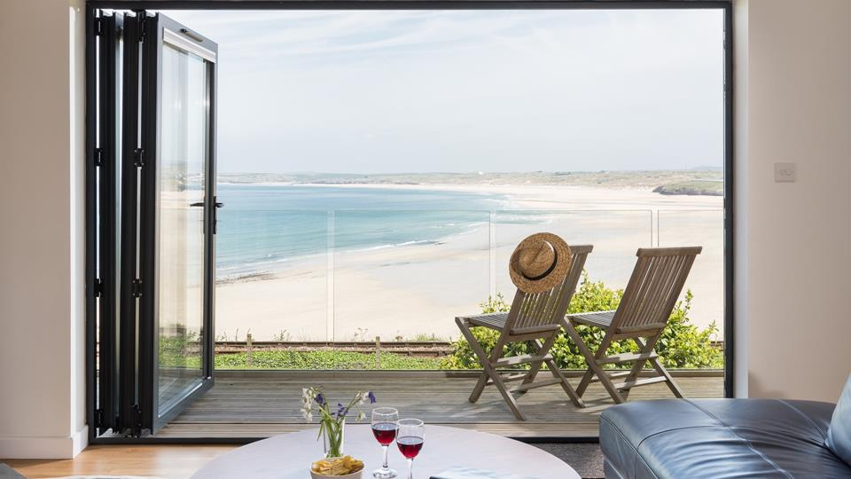 Bi-fold doors open out from the living space onto the glass front balcony overlooking the absolutely wonderful view over Carbis Bay.