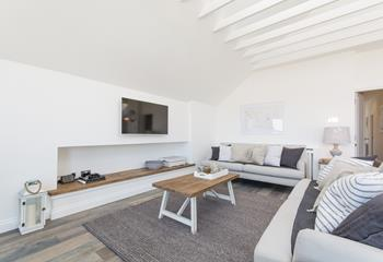 Comfy spacious sitting area with TV and games console.