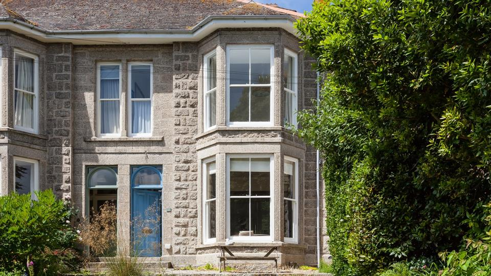Albany House facade has a Victorian style with granite facing stone and sash bay windows overlooking the garden.
