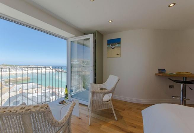 Patio doors open onto a Juliet balcony with sea and harbour views across St Ives.