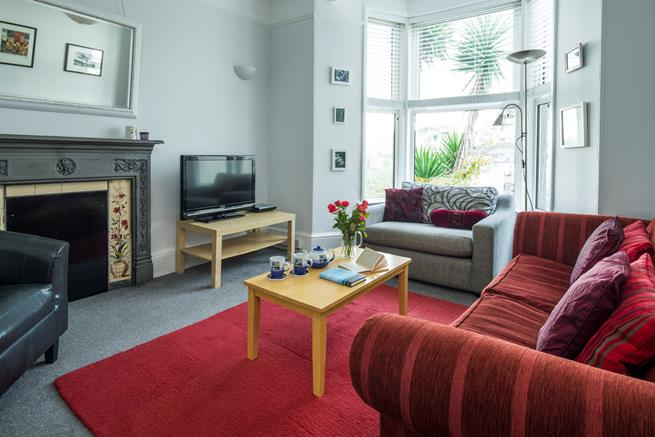 The comfy sitting room with sea views from the bay window