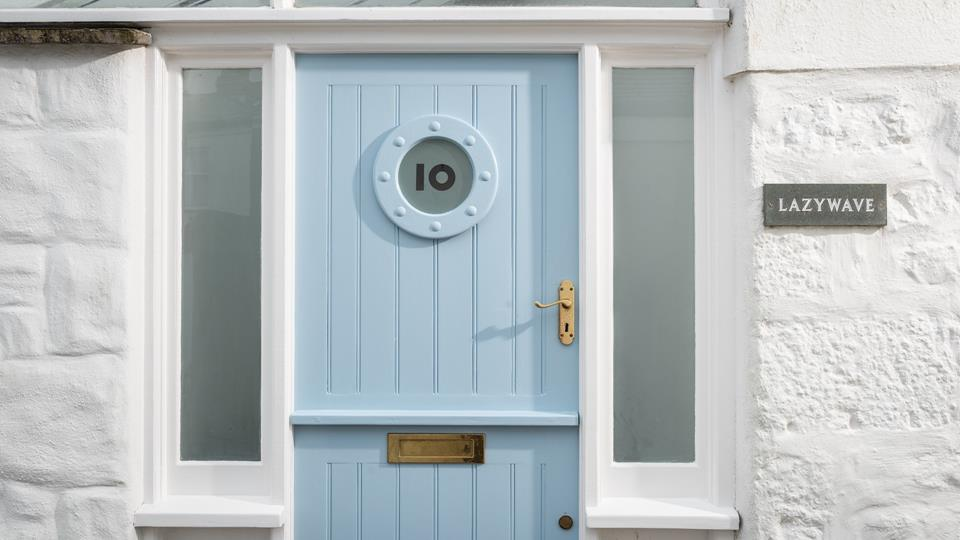 Lazy Wave is a whitewashed property with a pale Cornish blue stable entrance door and porthole insert glass.