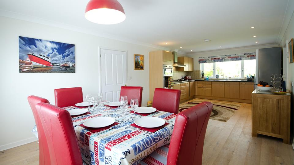 The dining area has red leather high-back dining chairs and a solid wood dining table.