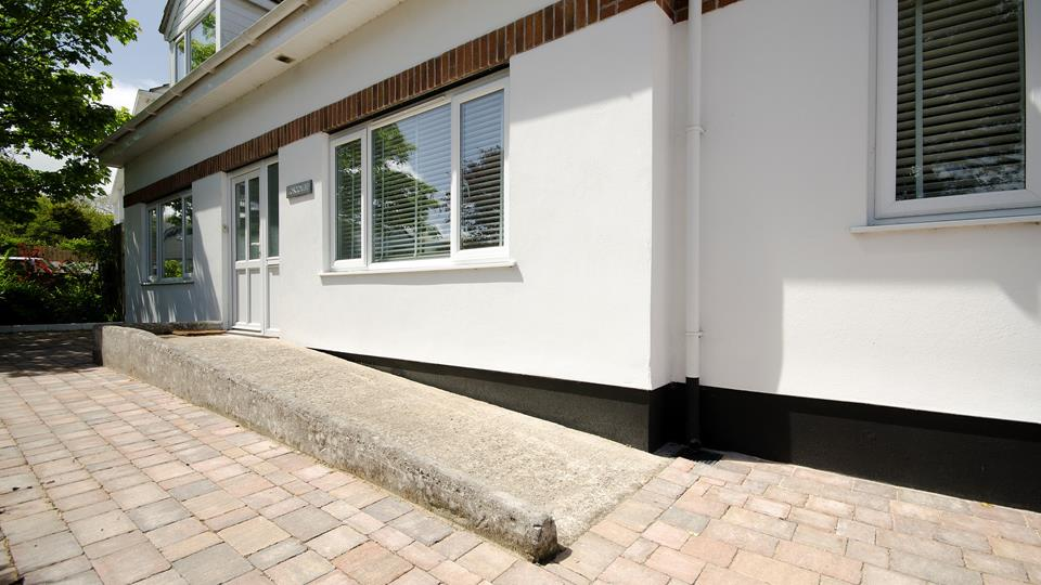 Loscombe front approach has ramp access from the brick-paved drive for easy access.