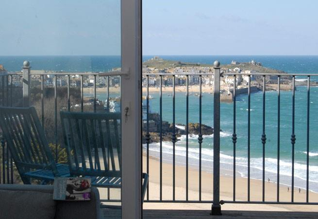 Full length sliding doors to decked balcony with sea and harbour view from the sitting room.