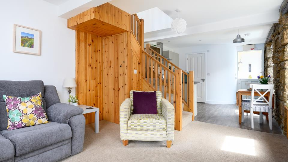 The living space has an exposed granite accent wall and a natural pine wood stairway.