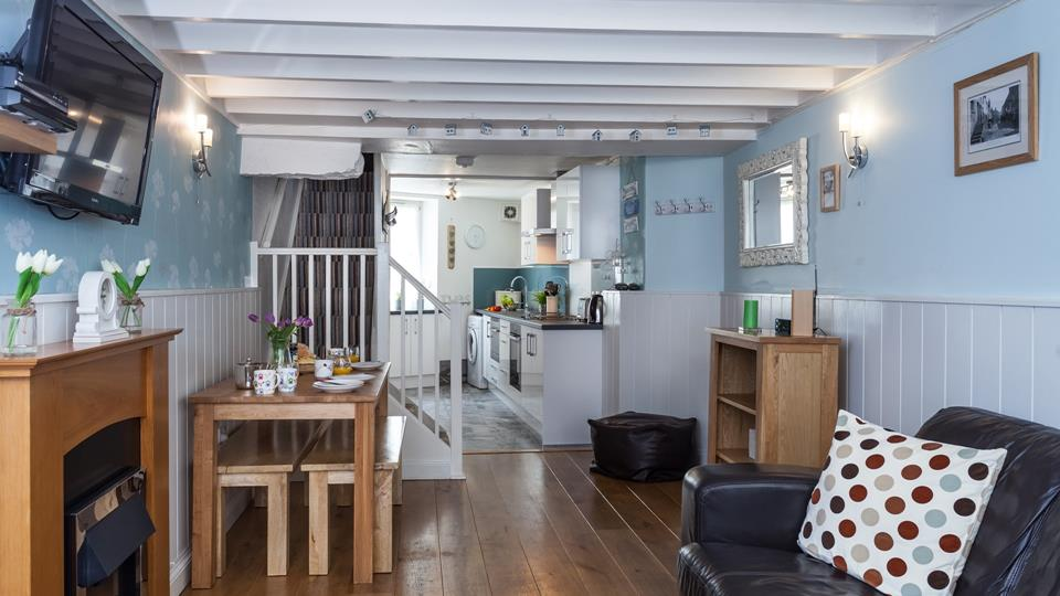 The living space has solid oak flooring, painted wood partial wall cladding and painted wood exposed beams.