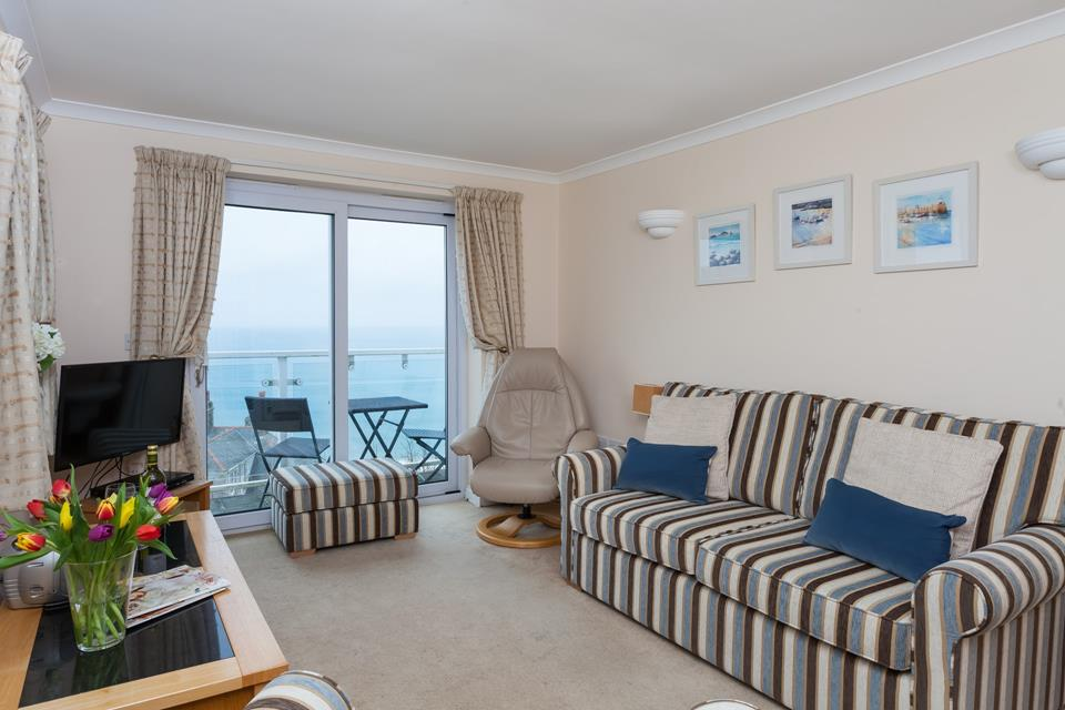 Comfortable seating in the sitting room with patio doors to balcony with superb sea views