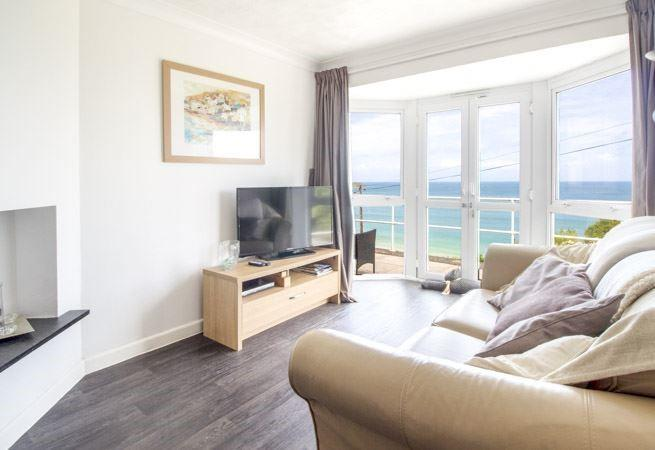 Sitting room with French doors leading out onto the patio area with superb sea views.