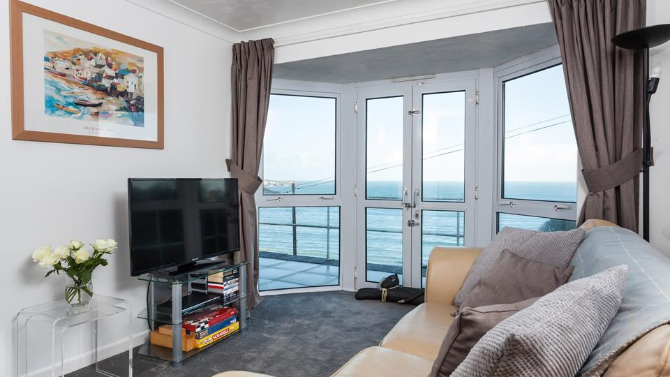 Large windows and patio doors offer breathtaking views across Carbis Bay beach.