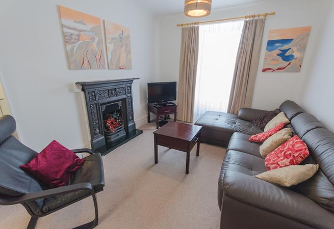 Sitting room with comfy seating and feature fireplace.