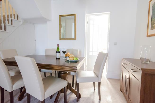 Dining area with dining table and six leather chairs.