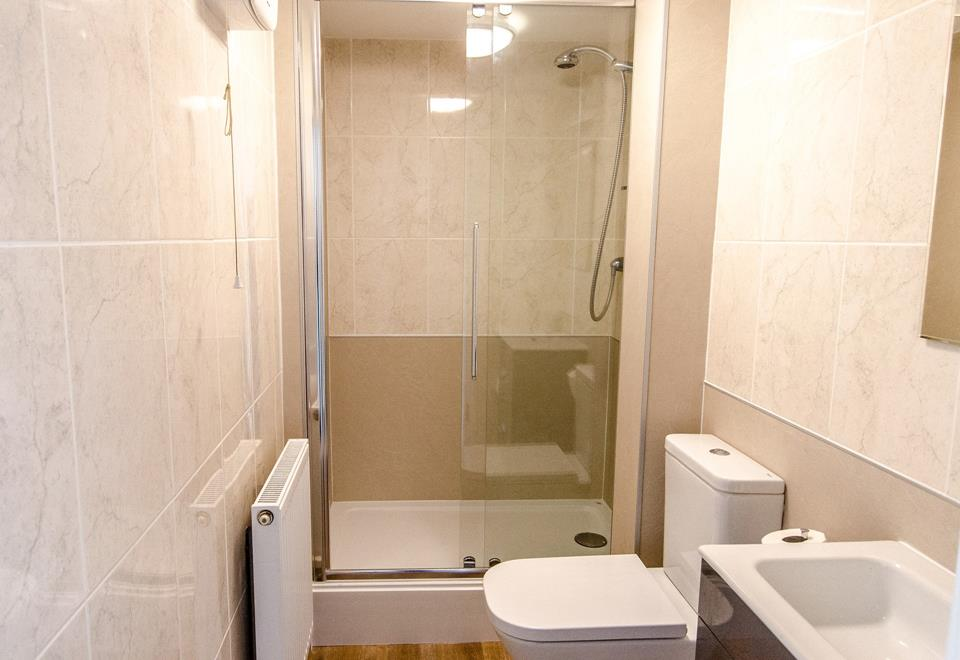 Shower room with large shower cubicle, WC and basin.
