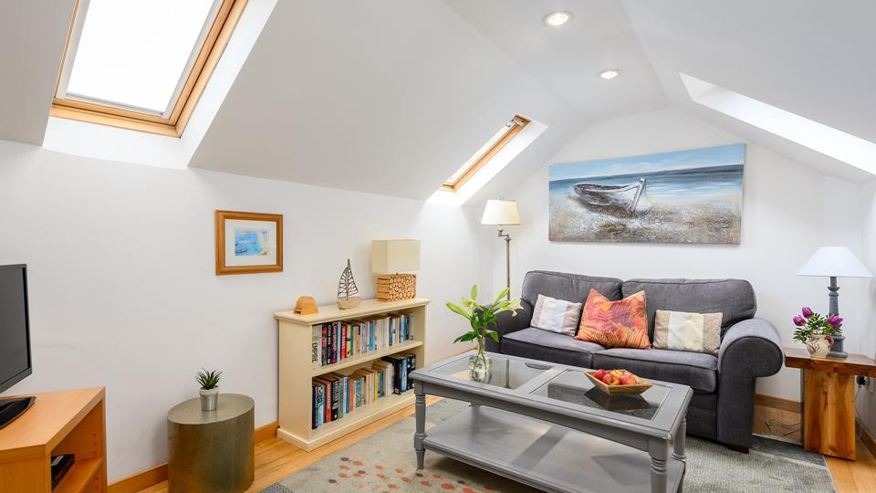 The living space is really light and airy, the natural solid wood flooring throughout with a large cosy rug.