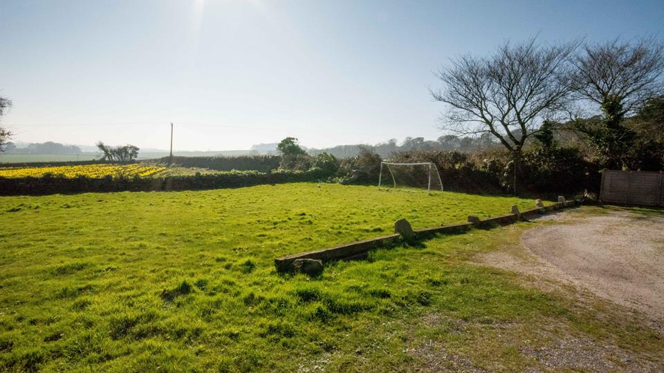 The outside area has a very large grass lawn, which is perfect for some family football fun.