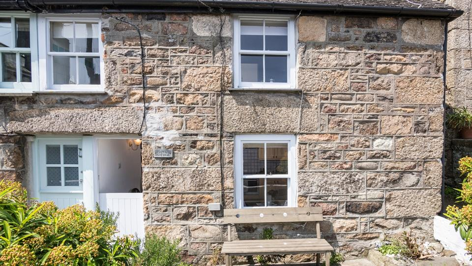 The small traditional cottage is set back from a narrow lane with very little traffic.