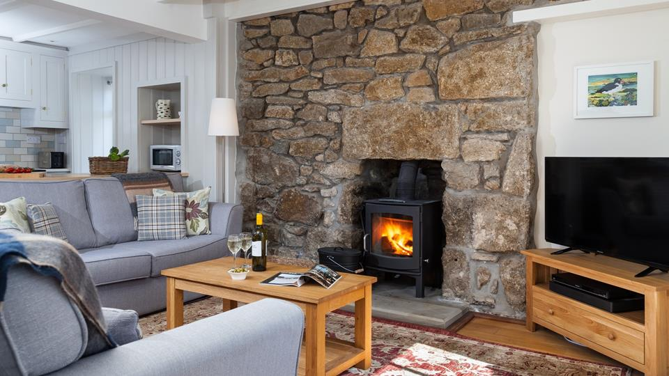 This charming cottage is finished with comfy sofas and a woodburner creating a homely getaway.