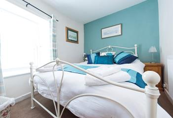 The bedroom has a comfy double bed and large window flooding the room with natural light.