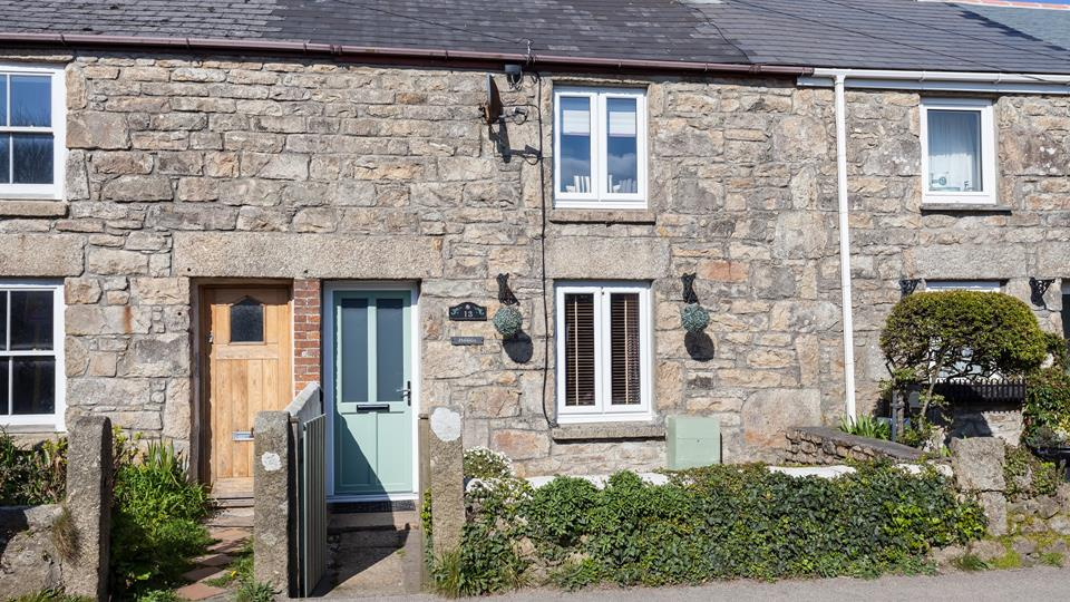 The cottage is accessed via a small painted wood gate with granite posts either side, granite slab and brick paving form the pathway and front courtyard.