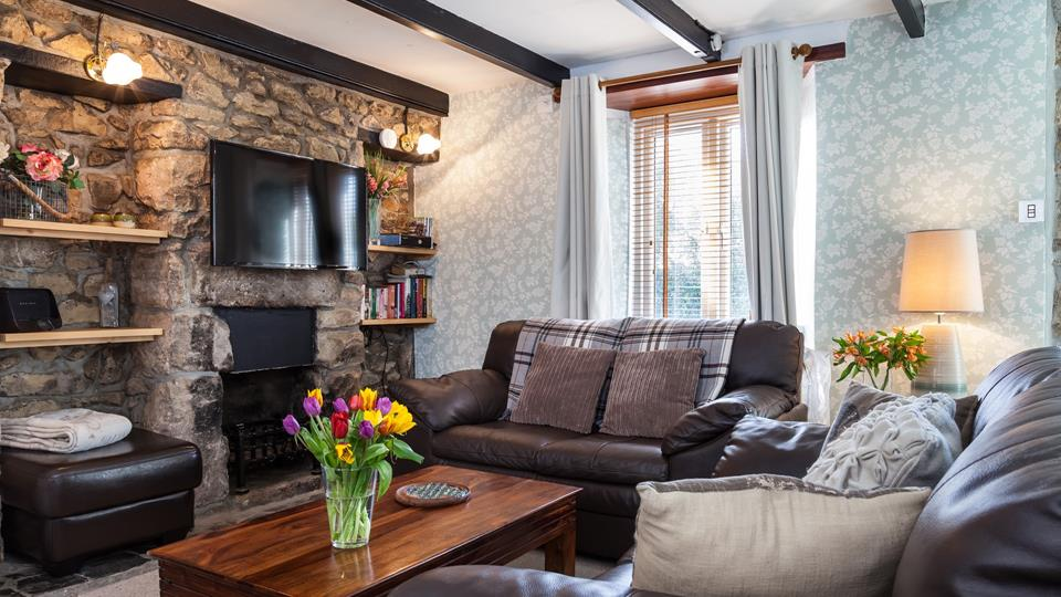 The living room has two leather sofas and a footstool with a natural wood coffee table.
