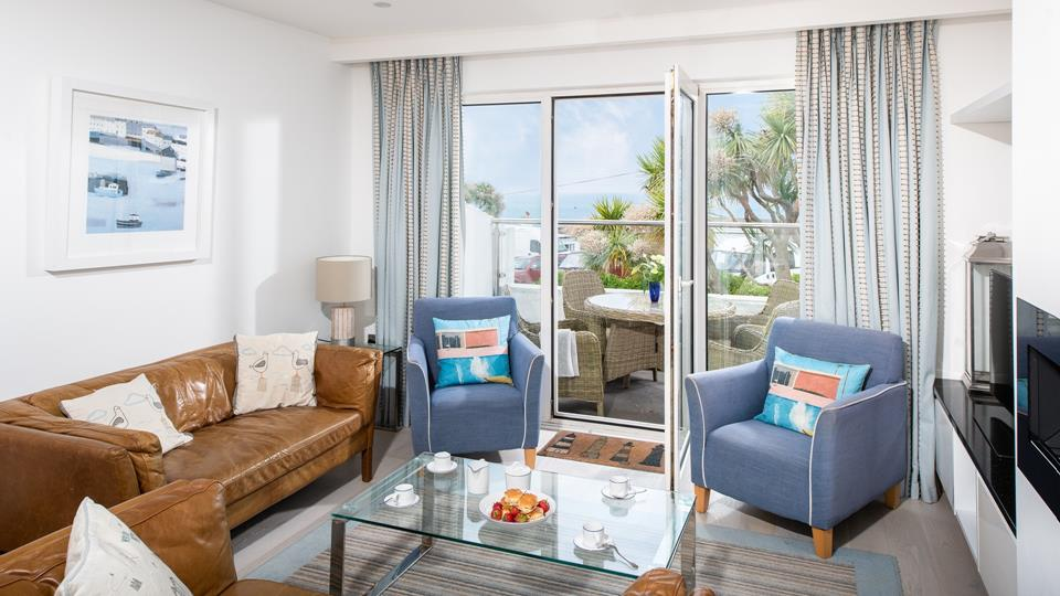 The living space has two leather and two textile armchairs with a metal and glass top coffee table.