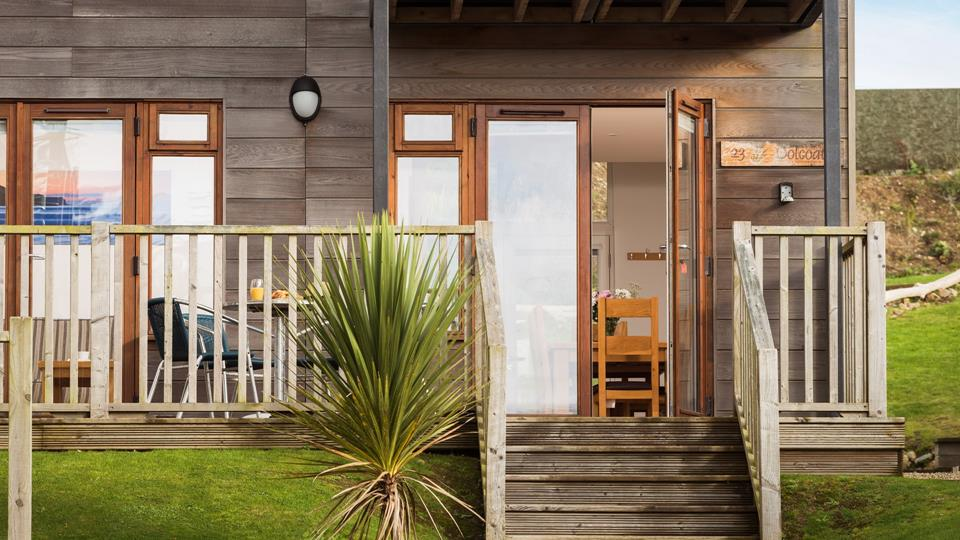 Five external wooden steps lead to the decked area and front door.